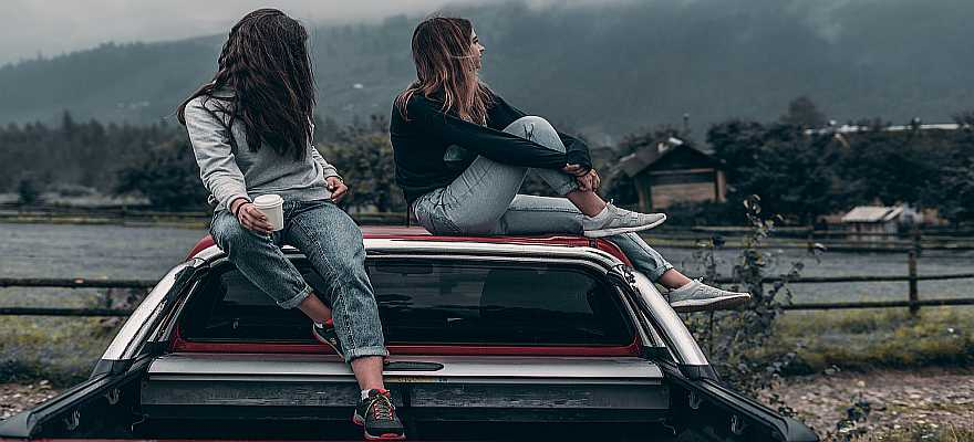 Two young women sitting on the roof and bed of a truck
